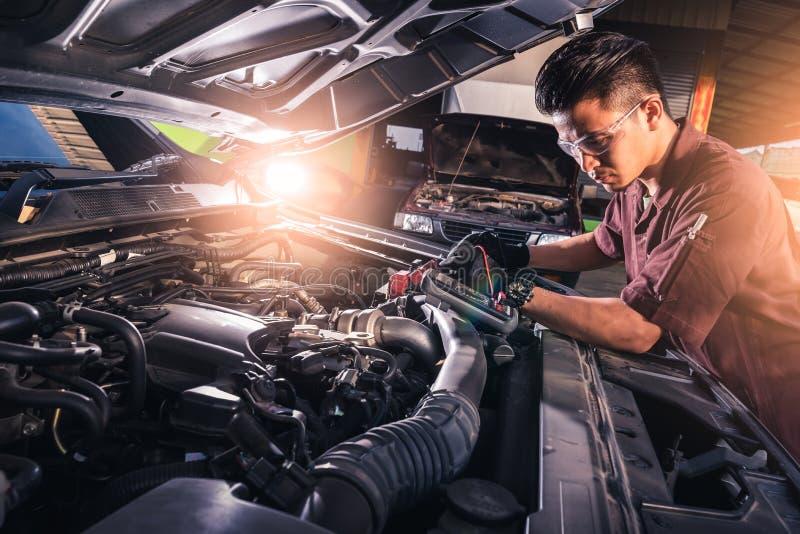 Das abstrakte Bild des Technikers, der Spannungsmeter f?r Spannungsmessung eine Autobatterie verwendet das Konzept von Automobil, lizenzfreies stockfoto