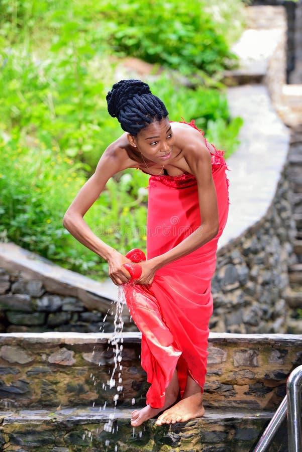 Das Afroamerikanermädchen, das im Park nahe dem Wasser stehen und das Löschen kleidet an stockfotografie