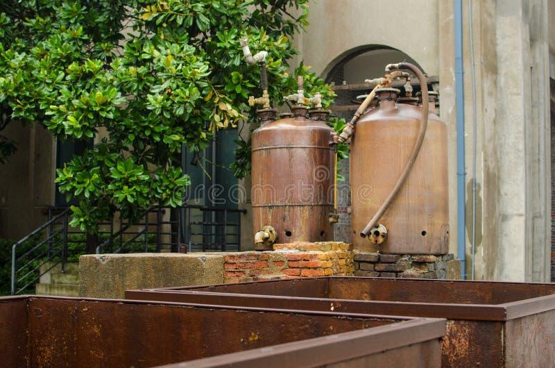 Das alte Dyehouse mit Dosen des destillierten Wassers stockfotos