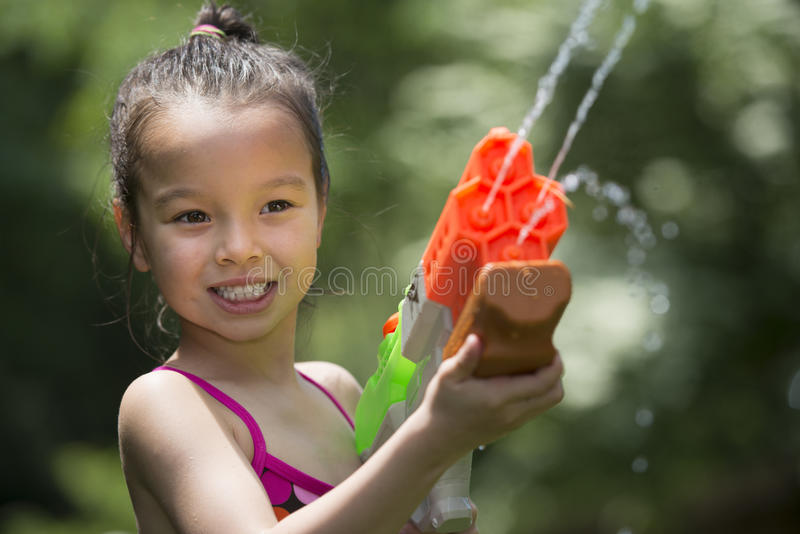 Das alte Fünfjahresmädchen, das mit spielt, spritzen Spielzeug stockfotos