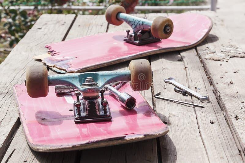 Das alte gebrochene Skateboard liegt mit einem Schlüssel auf einem Holztisch im Freien stockbild