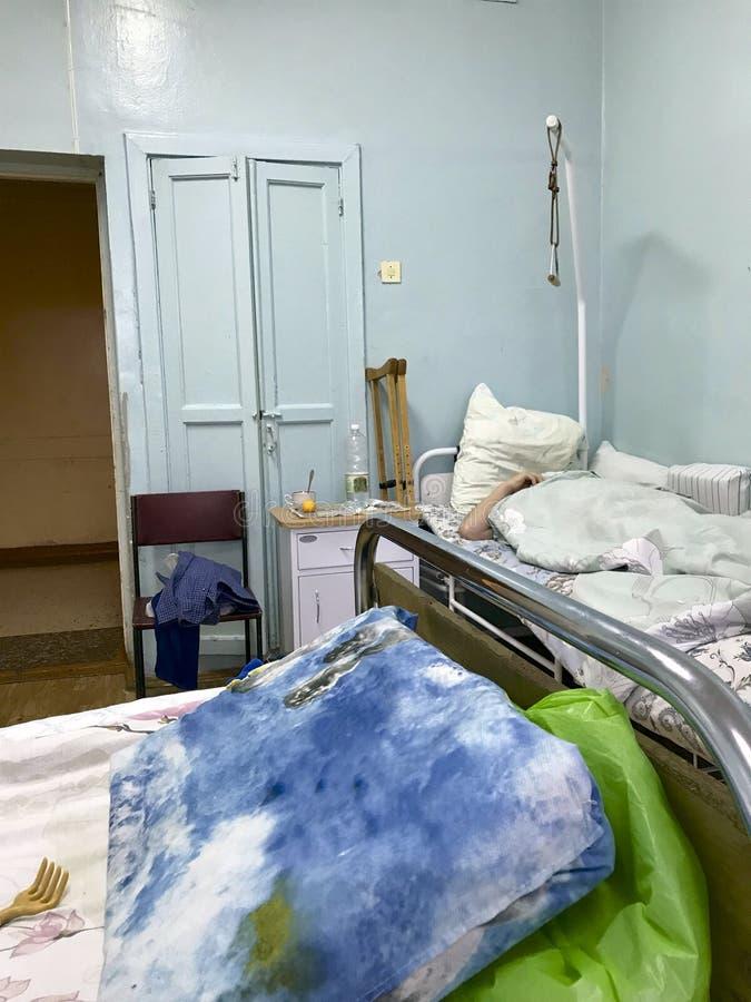 Das alte Krankenhaus vom Innere Gefüllte Betten von Patienten und von ihrem persönlichen Eigentum verließen auf den Betten und de lizenzfreies stockfoto