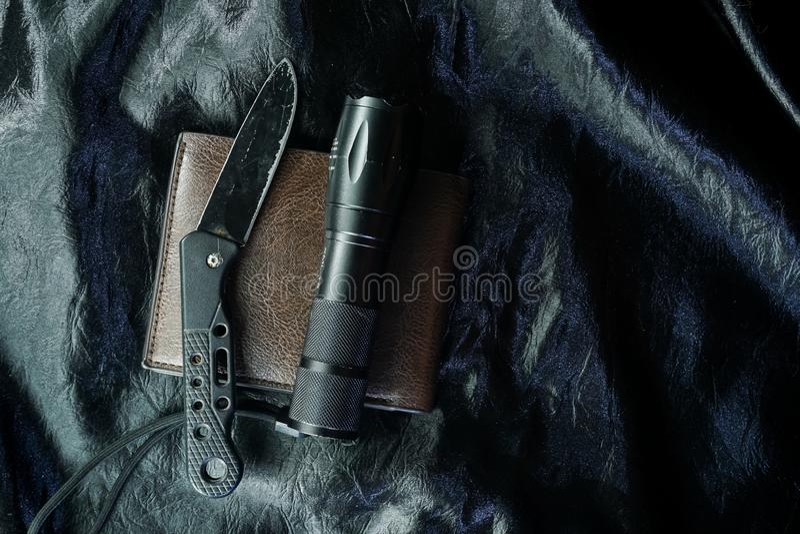 Das alte schwarze faltende Messer auf dem schwarzen Gewebe ist glänzend stockbild