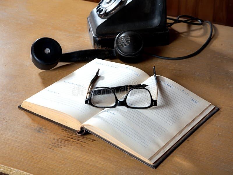 Das alte tägliche Protokoll mit Gläsern und Telefon lizenzfreie stockfotos