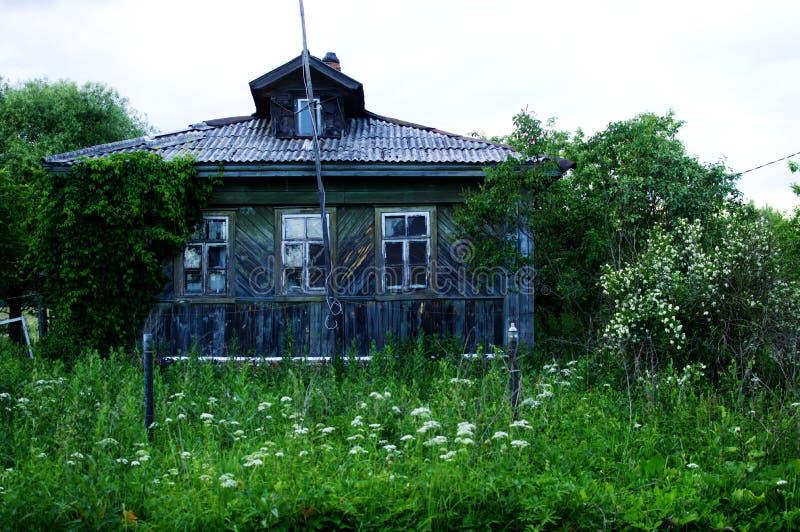 Das alte verlassene Holzhaus mit einem Garten stockbild