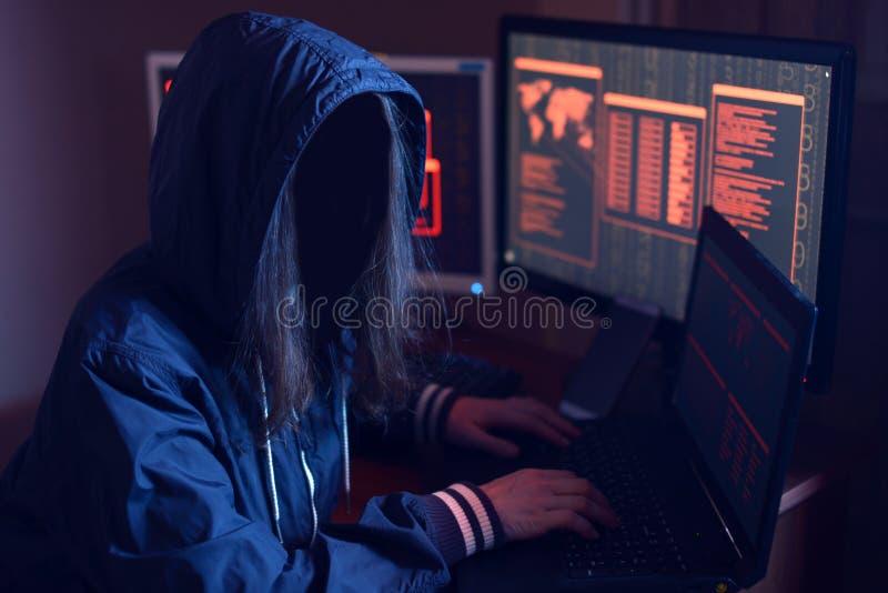 Das anonyme Hackermädchen ohne Gesicht den Code schreibend versucht, das System auf den Hintergrund-Bildschirmen im Neonlicht zu  lizenzfreie stockfotografie