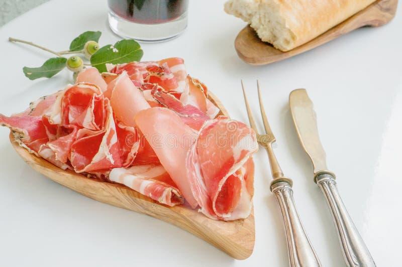 Das Aroma des Schinkens und der Gewürze, dünn geschnitten auf einer weißen Tabelle mit Brot antikem Tischbesteck und Rotwein stockfotografie