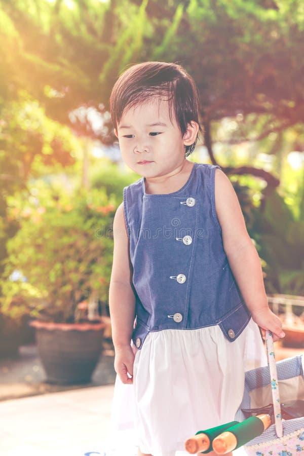 Das asiatische Kind, das Schaufel und Korb hält, bereitete sich zur Gartenarbeit vor vin stockbild