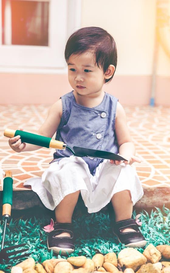 Das asiatische Kind, das Schaufel und Korb hält, bereitete sich zur Gartenarbeit vor vin stockfotografie