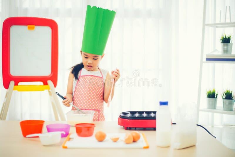 Das asiatische Kind, das Spaß mit dem Kochen und der Zubereitung des Teigs hat, backen Plätzchen in der Küche stockfoto