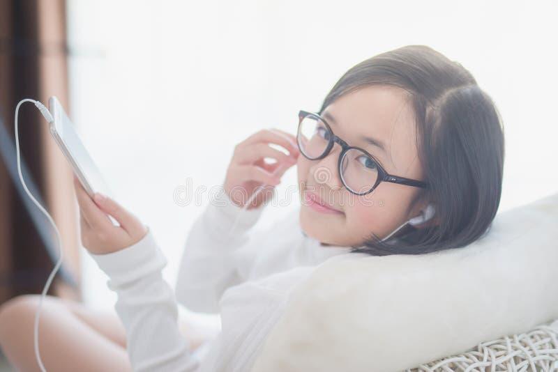 Das asiatische Mädchen, das Kopfhörer für verwendet, hören Musik stockfoto
