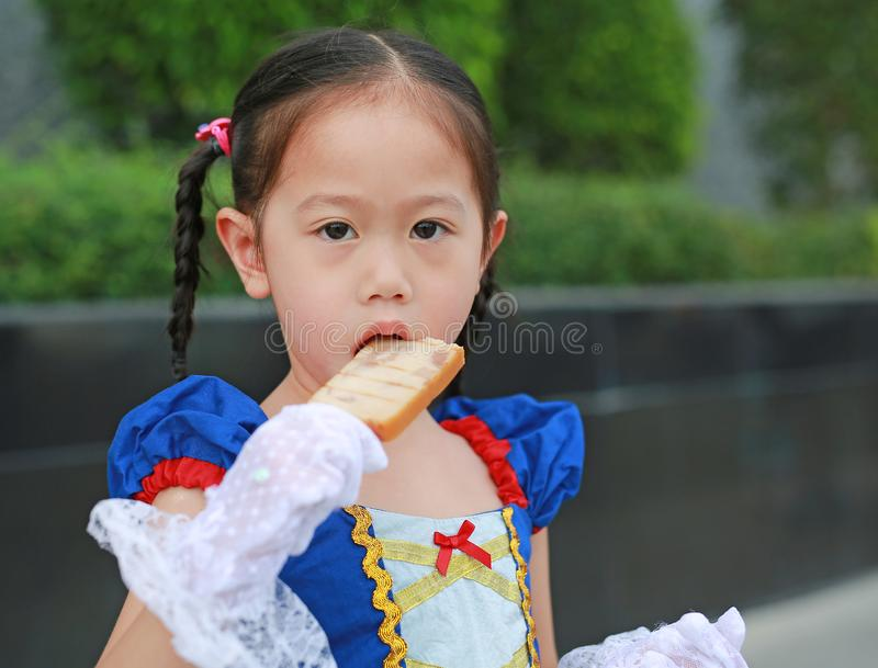 Das asiatische Mädchen, das mit einem Fantasiekostümessen gekleidet wurde, grillte geschnittenen Schinken auf Stock stockfotos