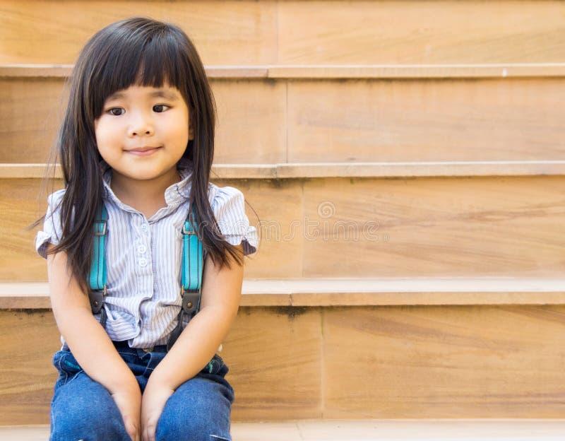 Das asiatische Mädchenlächeln, das auf gelber Treppe sitzt, zeichnet lizenzfreies stockbild