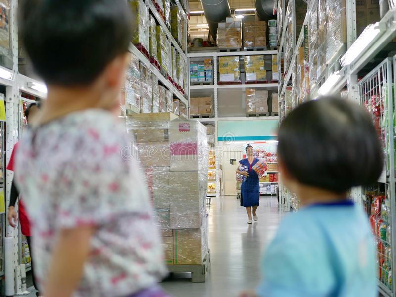 Das asiatische Muttereinkaufen für Snäcke in einem Bargeld und trägt für ihre Babys lizenzfreie stockbilder