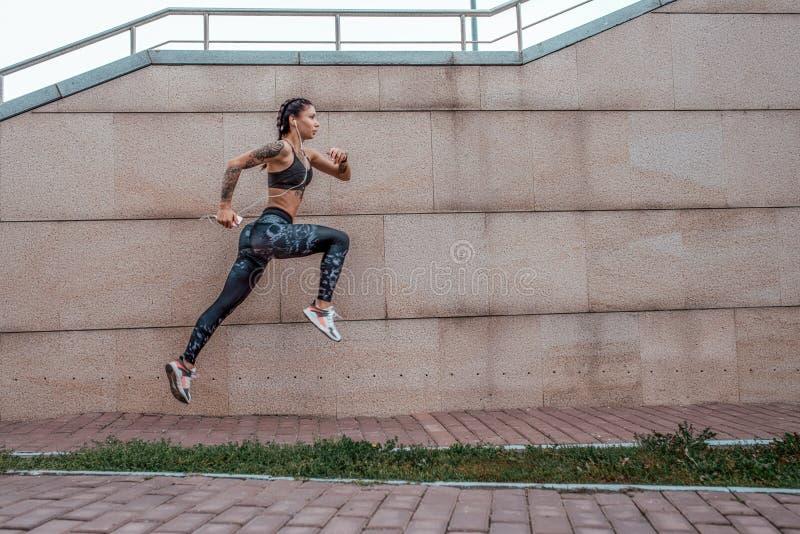 Das Athletenm?dchen l?sst Sprungssport Sommerstadt ausbildend laufen Kopfh?rer telefonieren Aktiver Lebensstil der Frischluft der stockbilder