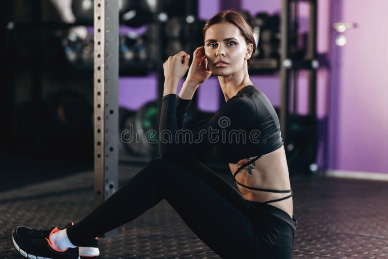 Das athletische dunkelhaarige Mädchen, das in der schwarzen Sportkleidung gekleidet wird, sitzt auf dem Boden in der Turnhalle na lizenzfreies stockfoto