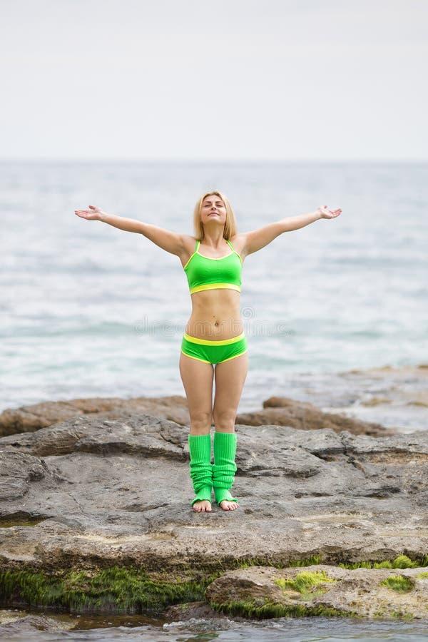 Das athletische Mädchen, das mit den Armen steht, hob gegen das Meer an lizenzfreies stockfoto