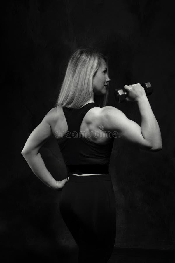 Das athletische Mädchen, das an Eignung teilnimmt, rüttelt Muskeln mit Dummköpfen in der Hand auf einem schwarzen Hintergrund lizenzfreies stockbild