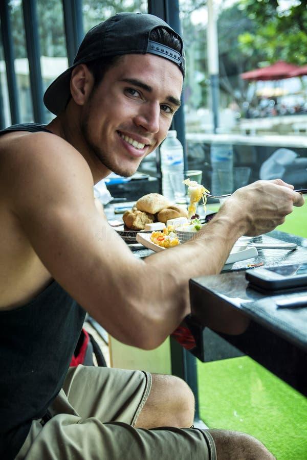 Das attraktive Frühstück des Junge-Mannes, Kuchen am Restaurant essend lizenzfreie stockbilder