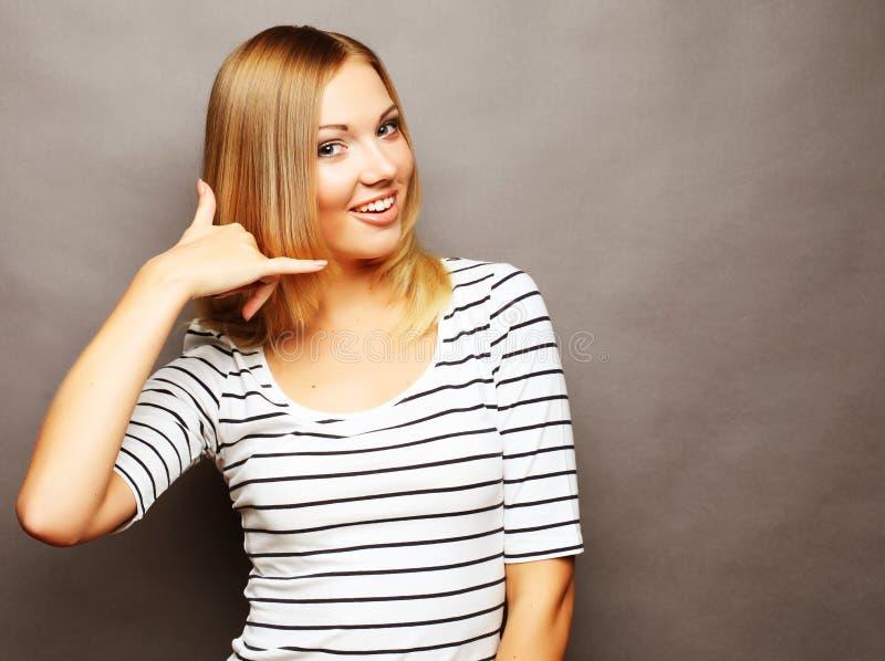 Das attraktive glückliche Mädchen, das mit den Fingern gestikuliert, rufen mich an stockfotografie