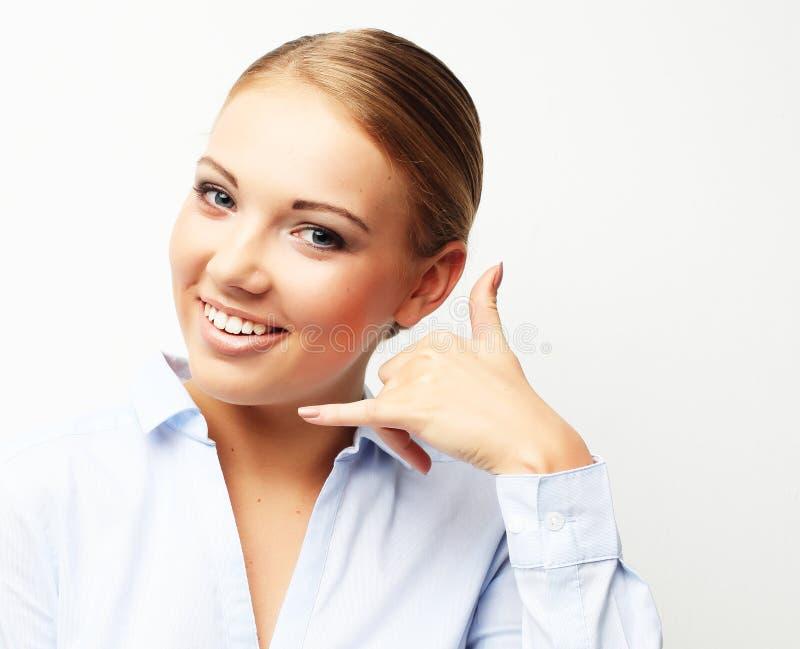 Das attraktive glückliche Mädchen, das mit den Fingern gestikuliert, rufen mich an lizenzfreies stockfoto
