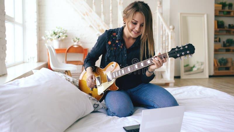 Das attraktive junge Mädchen, das lernt, E-Gitarre mit Notizbuch zu spielen, sitzen auf Bett im Schlafzimmer zu Hause lizenzfreies stockfoto