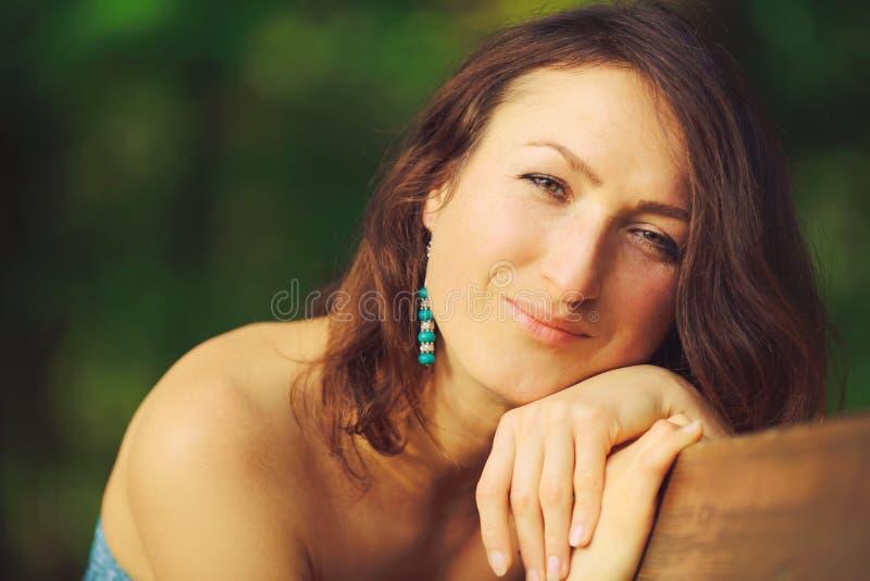 Das attraktive Mädchen, das auf der Bank im Holz eine Nahaufnahme aufwirft stockfotografie