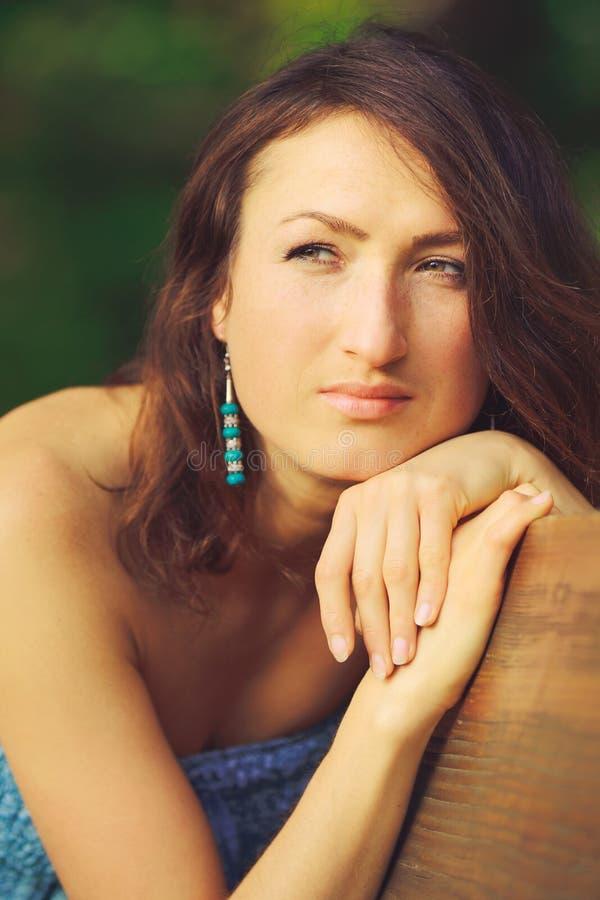 Das attraktive Mädchen, das auf der Bank im Holz eine Nahaufnahme aufwirft lizenzfreie stockfotos