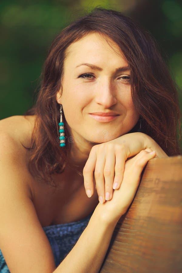 Das attraktive Mädchen, das auf der Bank im Holz eine Nahaufnahme aufwirft lizenzfreie stockfotografie