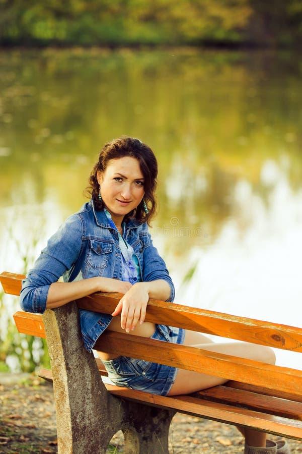 Das attraktive Mädchen, das auf einer Bank sitzt lizenzfreies stockfoto