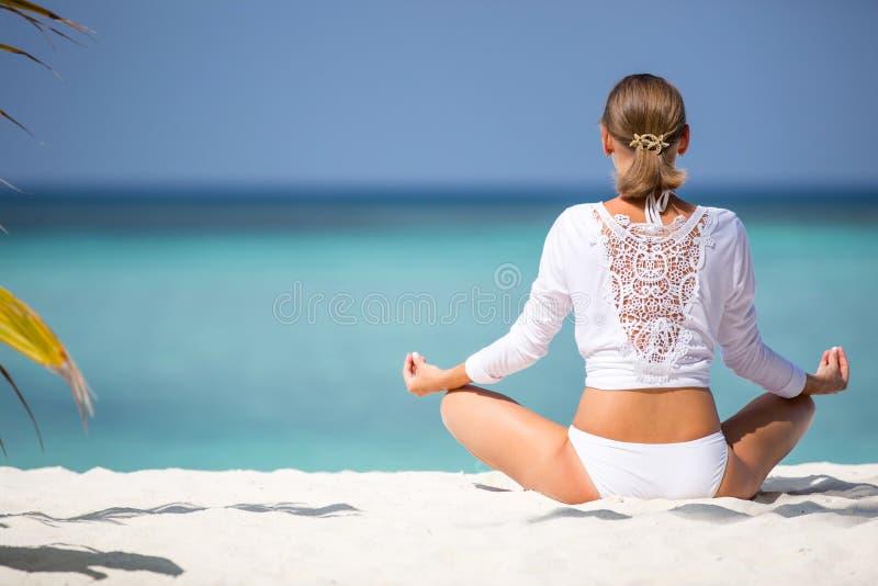 Das attraktive Mädchen im Weiß meditiert auf der Ozeanküste Malediven lizenzfreie stockfotos