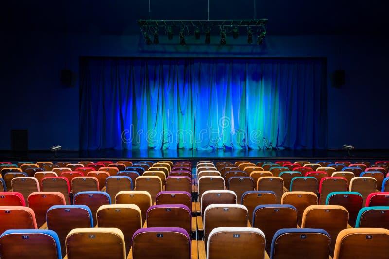 Das Auditorium im Theater Blaugrüner Vorhang auf dem Stadium Mehrfarbige Zuschauerstühle Hallenflutlicht der Beleuchtung equipmen lizenzfreie stockfotografie