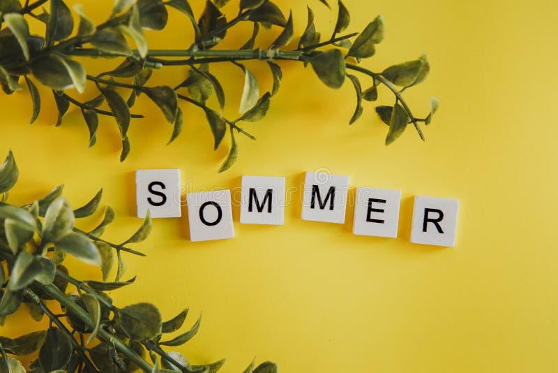 Das Aufschrift sommer auf Deutsch auf den Buchstaben der Tastatur auf einem gelben Hintergrund mit Blumen lizenzfreie stockbilder
