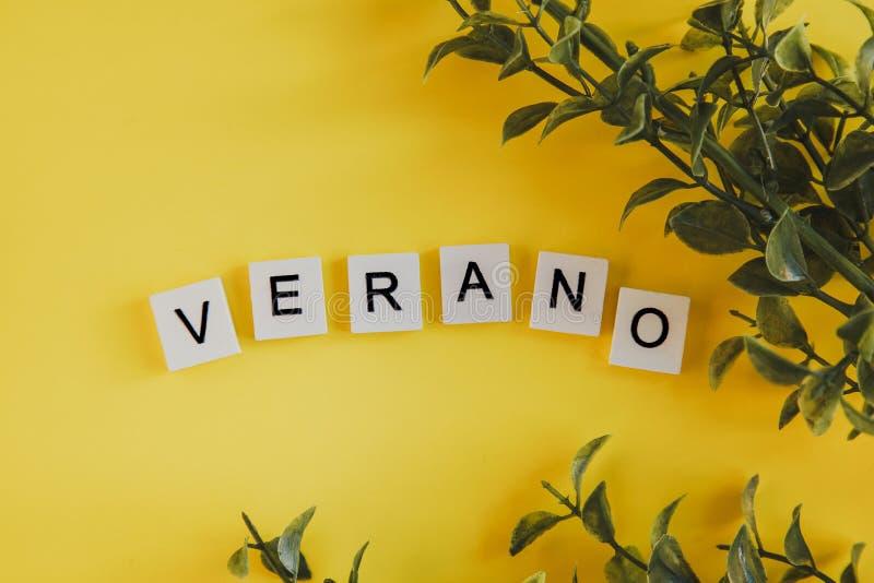 Das Aufschrift verano auf spanisch auf den Buchstaben der Tastatur auf einem gelben Hintergrund mit Niederlassungen von Blumen lizenzfreies stockbild