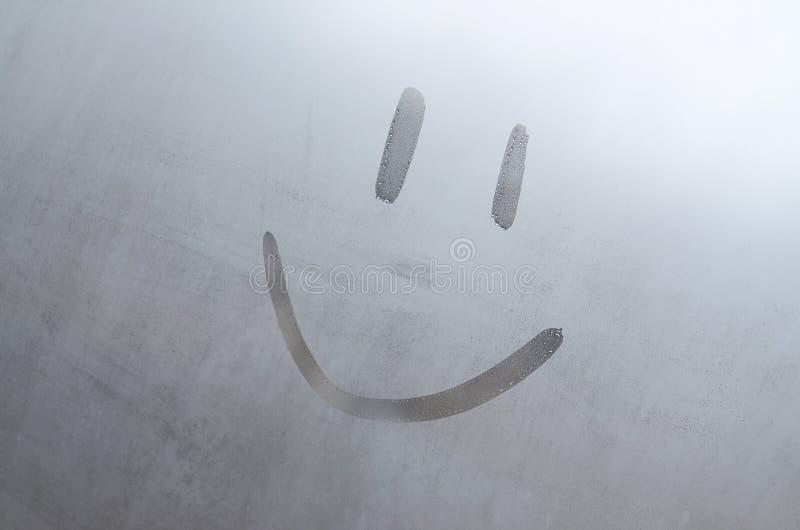 Das Aufschriftlächeln auf dem misted verschwitzten Glas Abstrakter Hintergrund stockfotos