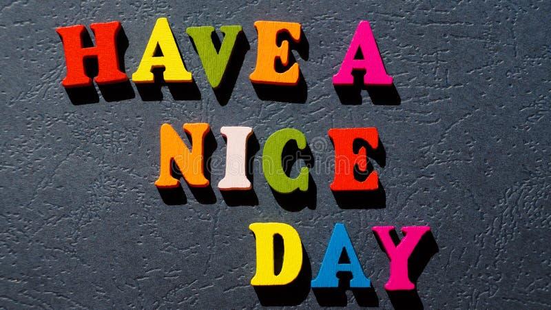 Das Ausdruck ` haben ein schöner Tag-`, das von den bunten hölzernen Buchstaben auf einer dunklen Tabelle gemacht wird lizenzfreies stockbild