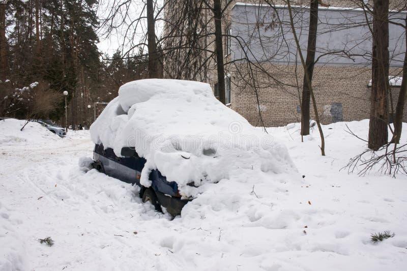 Das Auto, bedeckt mit starker Schneeschicht, im Yard des Wohnhauses in der provilcial Stadt lizenzfreie stockbilder