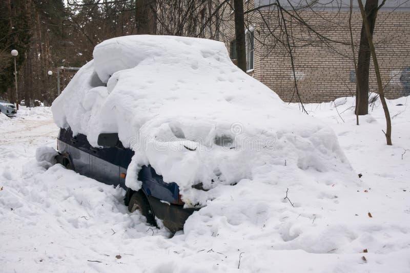 Das Auto, bedeckt mit starker Schneeschicht, im Yard des Wohnhauses in der provilcial Stadt stockbilder