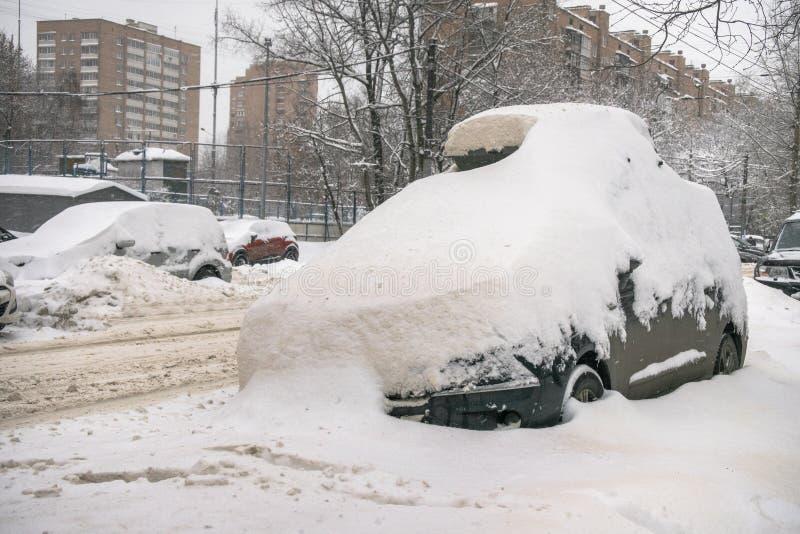 Das Auto, bedeckt mit starker Schneeschicht, im Yard des Wohnhauses in der provilcial Stadt lizenzfreies stockfoto