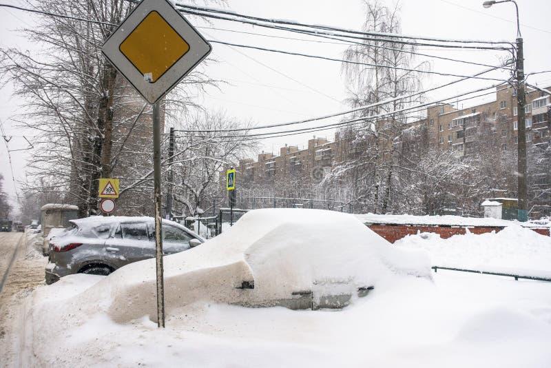 Das Auto, bedeckt mit starker Schneeschicht, im Yard des Wohnhauses in der provilcial Stadt stockbild