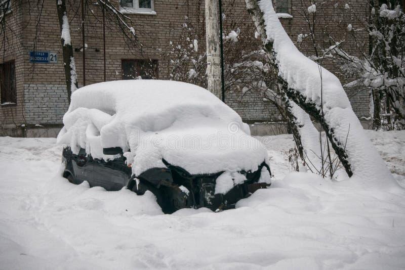 Das Auto, bedeckt mit starker Schneeschicht, im Yard des Wohnhauses in der provilcial Stadt lizenzfreies stockbild