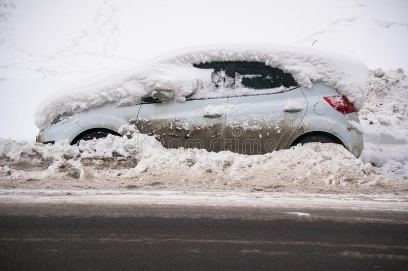 Das Auto, bedeckt mit starker Schneeschicht und Schlamm, auf der Fahrbahn lizenzfreies stockfoto