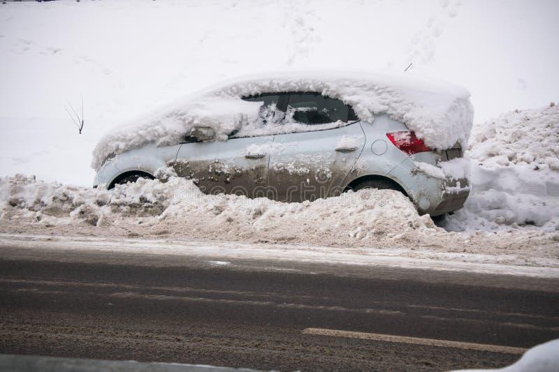 Das Auto, bedeckt mit starker Schneeschicht und Schlamm, auf der Fahrbahn stockfotos