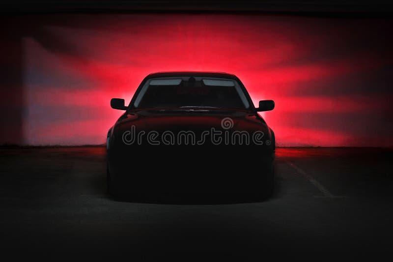 Das Auto in den Schatten mit glühenden Lichtern im Restlicht lizenzfreies stockfoto