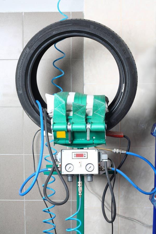 Das Auto hob auf den Aufzug und eine Schüssel für Schmierölwiedereinbau an Reparatur von Reifen - Vulkanisierung stockbild