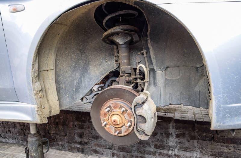 Das Auto ist hundert f?r Reparaturen Das Rad wird abmontiert Ersatz des Schocks stockfotos