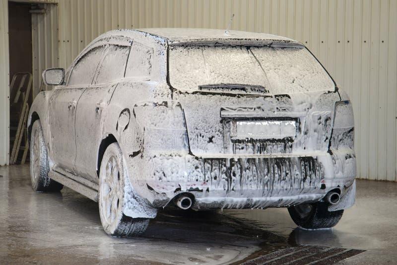 Das Auto wird mit dem Schaum an der Waschanlage bedeckt lizenzfreie stockfotos