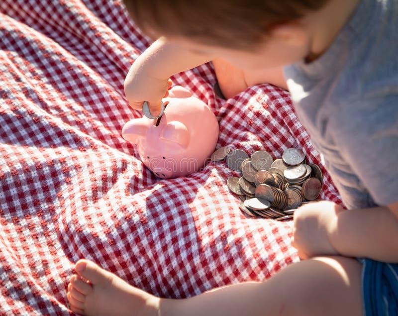 Das Baby, das auf Picknick-Decke sitzt, fügt Münzen in Sparschwein hinzu lizenzfreies stockbild