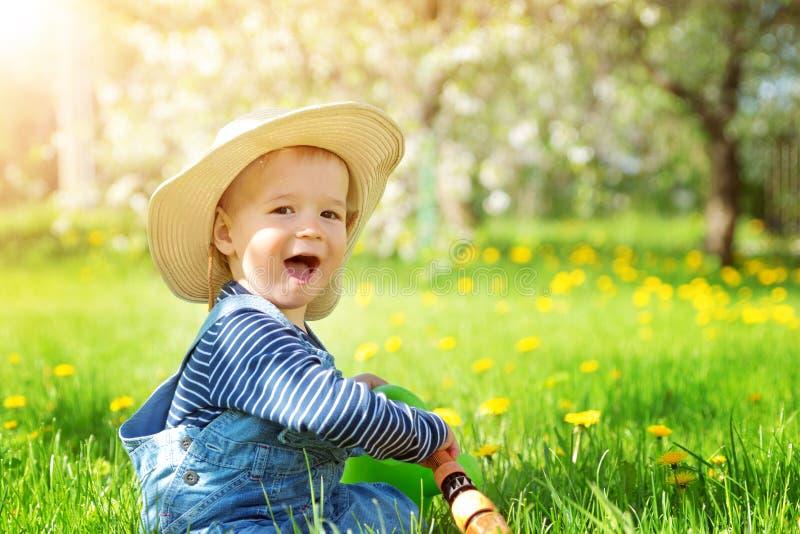 Das Baby, das auf dem Gras mit Löwenzahn sitzt, blüht im Garten lizenzfreies stockfoto