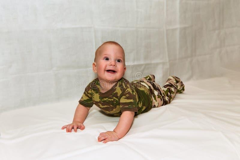 Das Baby in der Tarnung kleidet auf einem weißen Hintergrund stockbild